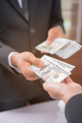 Businessman giving money to business woman,hand receiving money, US dollar