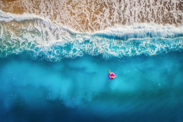 Aerial view of slim woman swimming on the pink swim ring in the transparent turquoise sea in Oludeniz,Turkey. Summer seascape with girl, beautiful waves, colorful water at sunset. Top view from drone