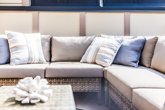 View of comfortable modern corner couch with many pillows outside on loft balcony with bright sun rays