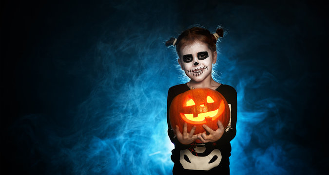 magic skeleton with  pumpkin. baby girl in costume to halloween.