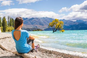 New Zealand travel tourist woman looking at Wanaka lone tree lake landscape. Girl relaxing enjoying view sitting on beach at Wanaka nature mountains outdoors.