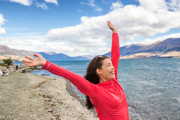 Wall Mural - Happy carefree freedom travel woman with arms up in joy on beach adventure in New Zealand. Asian girl tourist having fun screaming of excitement and happiness outdoors.