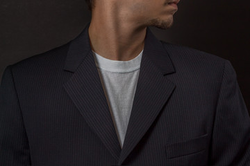 Image of young man in black suit jacket with white shirt underneath.