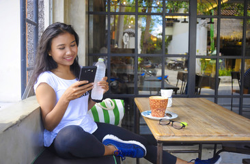 beautiful happy Asian woman smiling relaxed enjoying breakfast using mobile phone