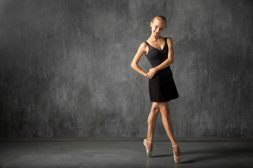 Beautiful attractive blonde woman baterina in a black dance tutu, white pantyhose and pointe shoes dancing in a dark studio