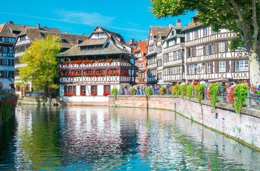 Typical house near water and flowers from La Petite France in Strasbourg, Alsace, France
