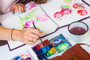 A close-up artist paints in the album for drawing a thin wooden tassel of pink flowers with watercolor, on the table lies a leather case with brushes, a mug of water, a palette of watercolors
