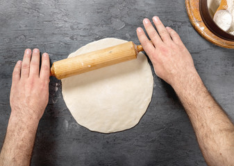 Wall Mural - Man preparing pizza dough in bakery, top view