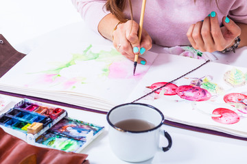 Close-up of a beautiful artist with bright nails draws a thin wooden brush and watercolor in the album for drawing on white paper pink peonies, on the terrace there is a watercolor, a mug with water