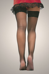 Young woman in short red dress and black sexy fishnet pantyhose stockings on her legs standing on the floor.