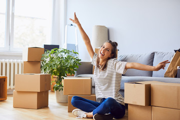 Young woman sitting in new apartment and raising arms in joy after moving in Wall mural