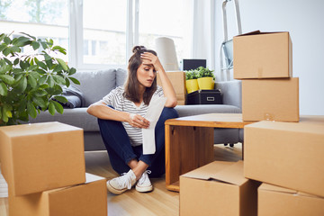 Worried young woman looking at bill sitting on floor in new apartment after moving in