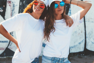 Models wearing plain tshirt and sunglasses posing over street wall
