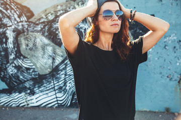 Model wearing plain tshirt and sunglasses posing over street wall