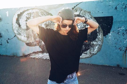 Model wearing plain tshirt and sunglasses posing over street wall