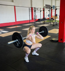 Woman In Sportswear Crouching While Lifting Barbell