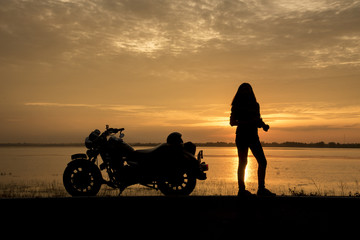 Beautiful Woman biker enjoying sunset, female riding motorcycle. motorbike driver traveling the world, Relaxing after long trip, freedom lifestyle. Travel Concepts.