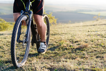 Closeup of cyclist man legs and hands riding mountain bike on outdoor trail in nature