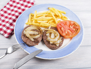 Hamburger with fries, onion and tomato on blue plate next to napkin, knife and fork on wooden table. Food.
