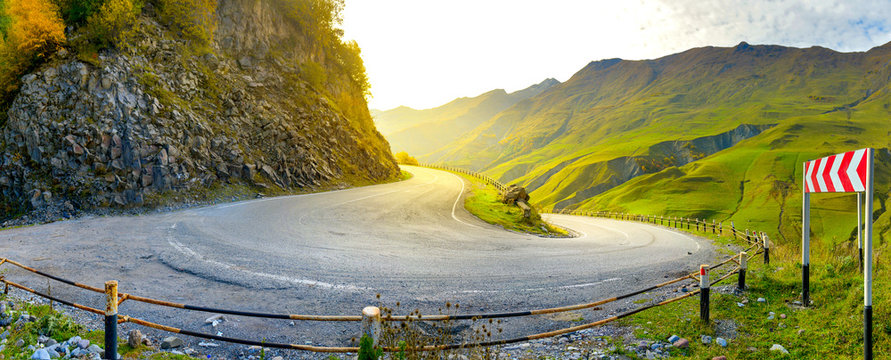 a sharp turn on a beautiful mountain road at sunset