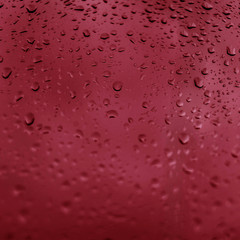 Drops of rain on red glass background. Natural Pattern of raindrops. Rain in the city.