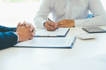 Business young man in shirt insurance agent showed the contract and pointing it while sitting together with man at the desk in office