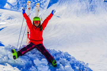 Girl sitting with arms spreading wide open on the fresh powder snow at sunny day in mountains. Swiss Alps.