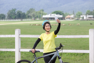 Middle aged women take self photo with phone on her bicycle