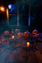 The concept of Halloween. A lot of luminous evil scary pumpkins, jack lantern, with candles, leaves and clouds and a moon outside the window with a warm and cold blue light on wooden floor in smoke