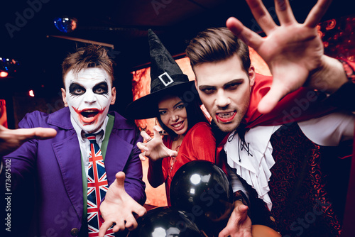 Halloween party. Adult people in terrible costumes for a party for Halloween posing with scary faces
