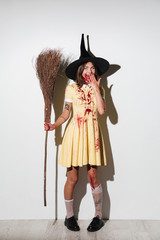 Full length image of happy woman in halloween costume