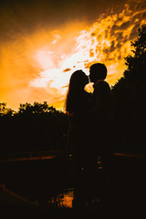 Beautiful young couple on the sunset background