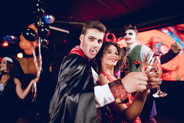 A guy dressed as a vampire and a girl dressed as a demon posing with champagne glasses. Their friends are having fun