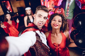 A guy dressed as a vampire and a girl dressed as a demon posing and making selfie on their smartphone