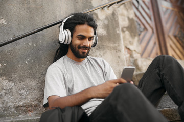 Casual young hipster with dreadlocks listening music holding mobile phone.
