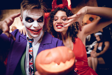 Halloween party. A guy in a Joker costume and a girl in a demon costume posing with a pumpkin-lamp.
