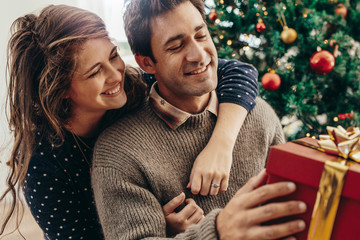 Young couple having fun celebrating Christmas with gifts.