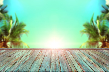 Empty Old wooden table top isolated on coconut trees and blue sky background, Idea for display or put your products.