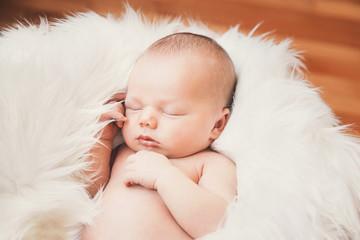 Sleeping newborn baby in a wrap on white blanket.