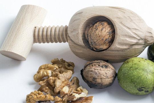 Noix et casse noix de fabrication artisanale en bois sur fond blanc