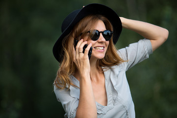Portrait of a model girl talking on the phone in the summer outdoors. Beauty, style, summer.