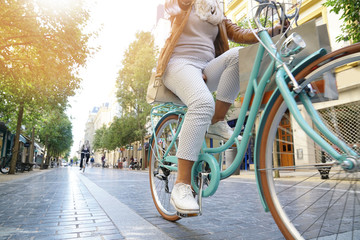 Senior woman riding city bike in town Wall mural