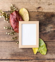 Flat lay photo frame with autumn leaves on old table. Rustic mock up, background