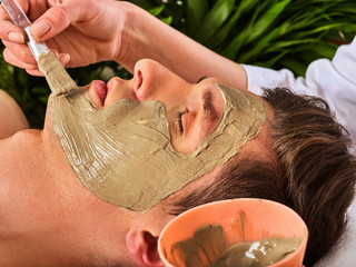 Mud facial mask of man in spa salon. Massage with clay full face. Girl on with therapy room. Man lying wooden spa bed. Green palm leaves in the background. Close-up of a man's face.