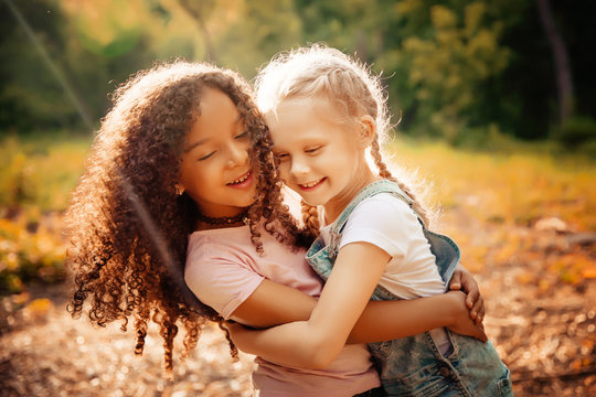 Two happy girls as friends hug each other in cheerful way. Little girlfriends in park.