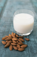 Glass Of Almond Milk On Blue Wooden Background With Almond Nuts