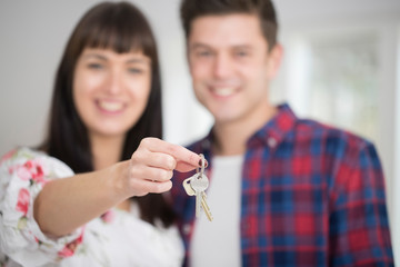 Portrait Of Young Couple Holding Keys To New Home