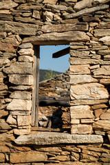 Verfallene alte Ruine aus Natursteinen mit Fensteröffnung und Ausblick zum Himmel