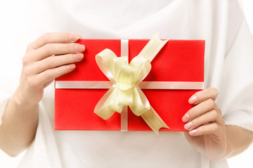 red gift with a bow in the female hands.