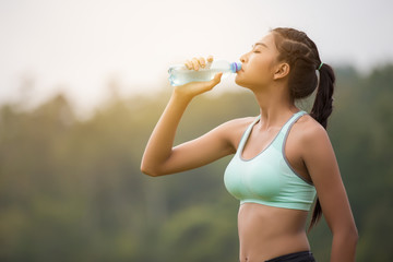 Asian young woman drinking water sunny morning after jogging.